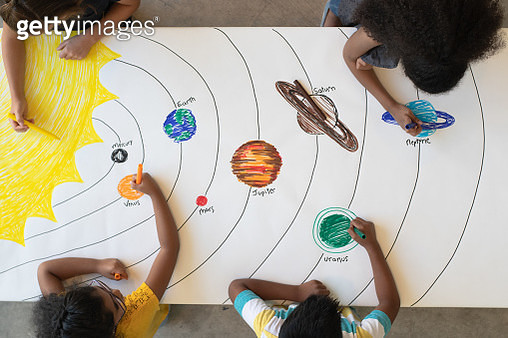 A group of multi-ethnic elementary students sit around a table covered in white coloring paper. They each have a marker in their hands and are working on drawing a solar system.  One girl is coloring in the sun and the other students are working on indivi - gettyimageskorea