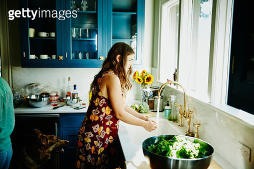 Woman washing hands at kitchen sink in home while preparing dinner - gettyimageskorea