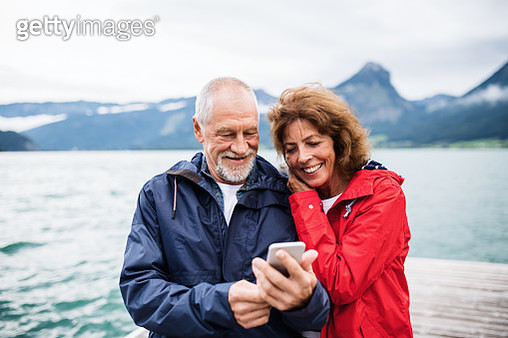 Cheerful senior couple tourist standing by lake in nature on holiday, using smartphone. - gettyimageskorea