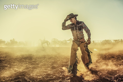 A cowboy walking in the dust at a rodeo after being thrown off a bronco. - gettyimageskorea