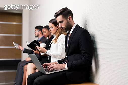 Group of business men sitting on bench in office - gettyimageskorea