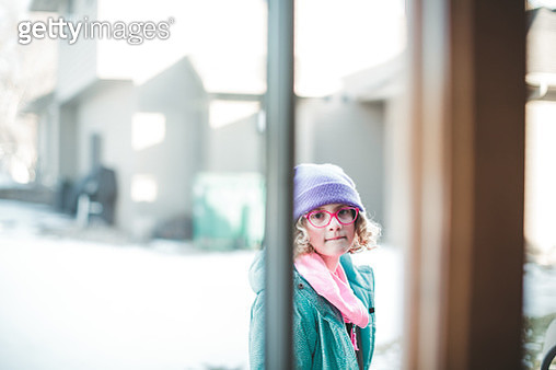 Girl looks through an open window while standing outside bundled up in winter clothing on a snowing day. - gettyimageskorea