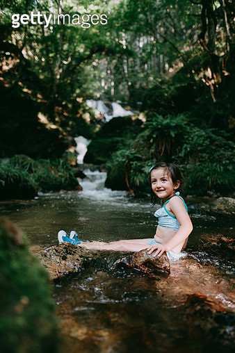 Portrait of cute Eurasian little girl playing in river water in forest - gettyimageskorea