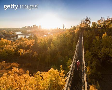 AERIAL view as woman runs on urban bridge in autumn - gettyimageskorea