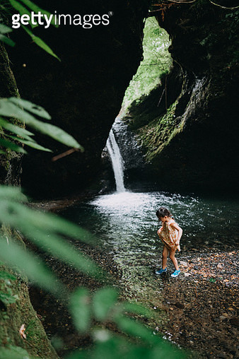 Portrait of little girl walking in river water running from waterfall, Japan - gettyimageskorea
