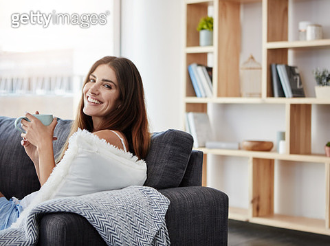 Shot of a young woman enjoying a cup of coffee while relaxing in the lounge - gettyimageskorea