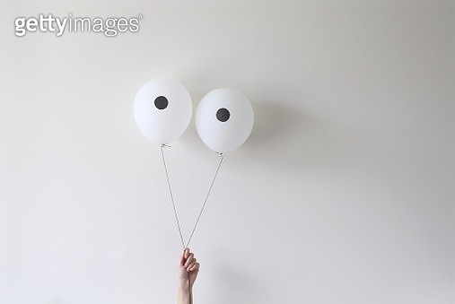 A hand holding a pair of balloons that look like eyes - gettyimageskorea