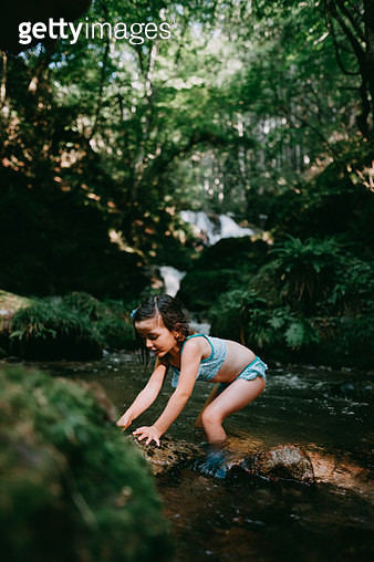 Portrait of cute 4 year old girl playing in river water in forest - gettyimageskorea