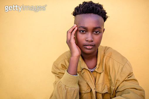 Portrait of a serious young woman wearing yellow jacket in front of yellow wall - gettyimageskorea