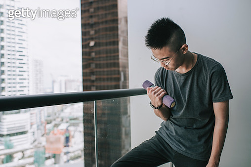 one asian chinese teenager boy workout with his dumbbell muscular build in the balcony - gettyimageskorea