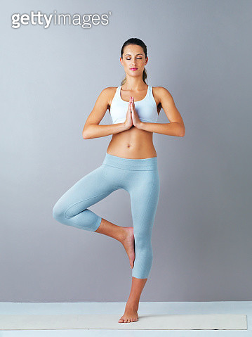 Full length shot of an attractive and sporty young woman practicing yoga against a grey background - gettyimageskorea