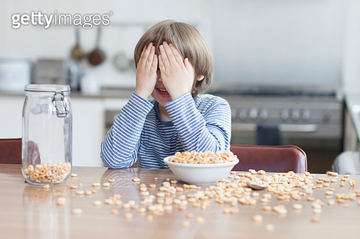 Boy eating bowl of cereal in kitchen - gettyimageskorea