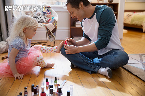 Father painting daughter toenails with fingernail polish - gettyimageskorea