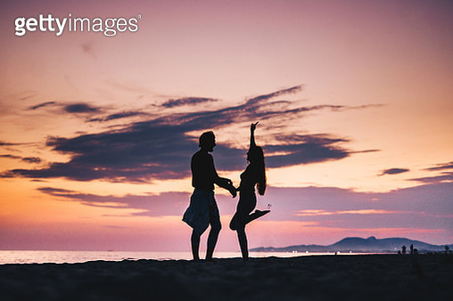 Silhouette of a playful couple having fun on the beach at sunset. - gettyimageskorea