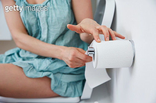 Woman on toilet reaching for toilet paper - gettyimageskorea