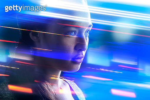 Young woman standing with speeding lights swirling around her - gettyimageskorea