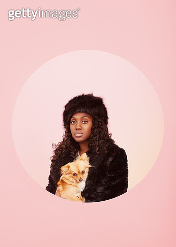 Studio portrait of black woman with fur hat and jacket and small dog on her lap - gettyimageskorea