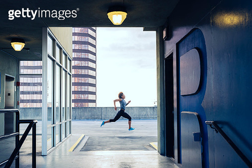 Young woman running on the roof of a parking garage in an urban location - gettyimageskorea