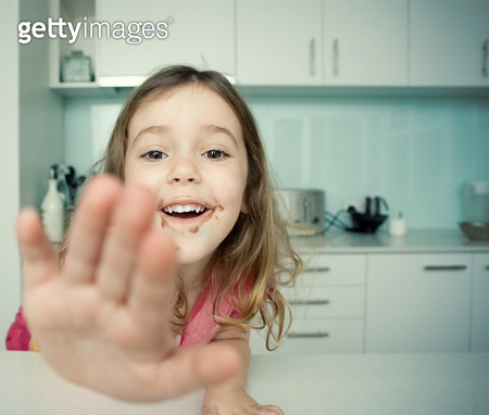 Young girl in the kitchen with chocolate on her fa - gettyimageskorea