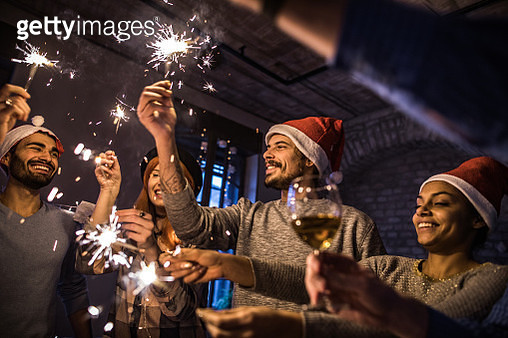 Young happy colleagues having fun with sparkles on Christmas Eve in the office. - gettyimageskorea