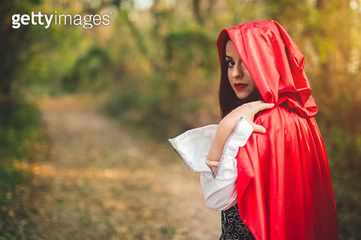 Little red riding hood looking towards sunset, seems to be lost in the forest. Waist up. - gettyimageskorea