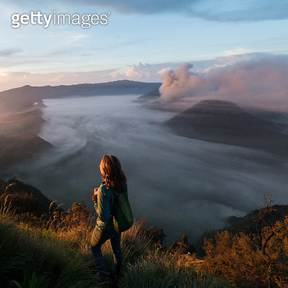 Young Caucasian woman standing and  looking at  Bromo volcano at sunrise, Java, Indonesia - gettyimageskorea