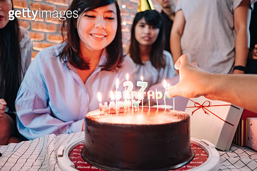 Young Women Blowing Out Candles on Birthday Cake with Friends - gettyimageskorea