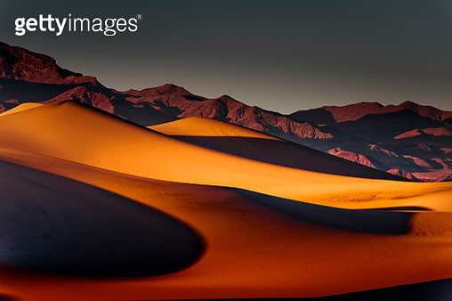 The soft flowing beauty of the panoramic oceanic mountainous sand dunes contrasted with the distant harshness of the rocky peaks; both grasping the heat and light from the sun's evening rays. - gettyimageskorea