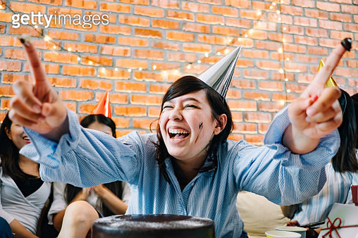 Playful Women Celebrating Birthday With Friends - gettyimageskorea