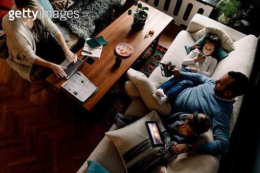 High angle view of family using various technologies in living room at home - gettyimageskorea