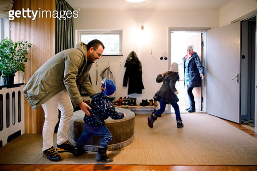 Playful siblings with parents in mudroom at home - gettyimageskorea