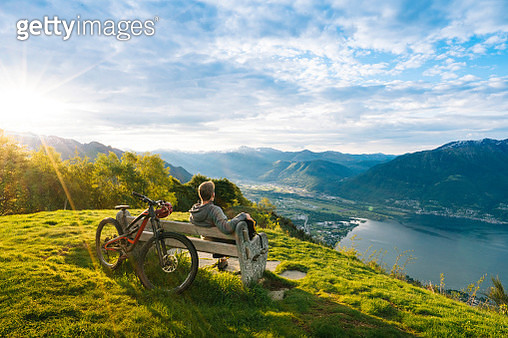 He sits on bench in alpine meadow; sun rises over ridge crest behind - gettyimageskorea