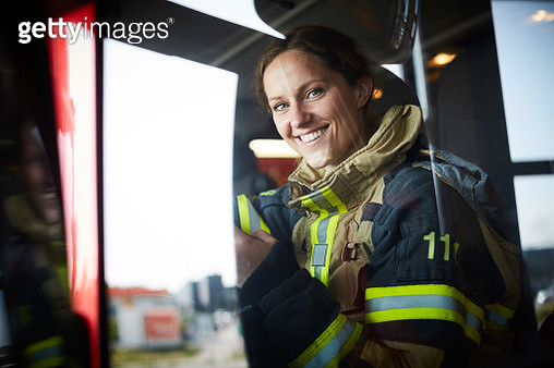 Portrait of smiling female firefighter sitting in fire engine - gettyimageskorea