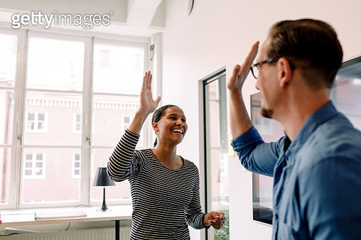 Happy businesswoman giving high-five to male colleague in office - gettyimageskorea