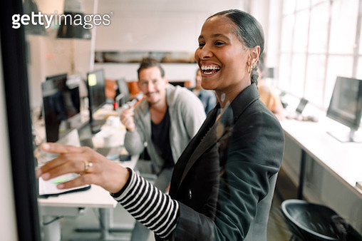 Smiling businesswoman discussing with coworker seen through glass at office - gettyimageskorea