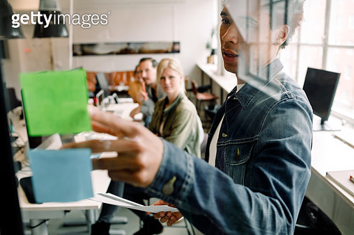 Businessman showing adhesive note to creative team seen from glass at workplace - gettyimageskorea