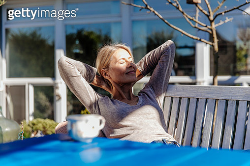 Woman relaxing on garden bench - gettyimageskorea