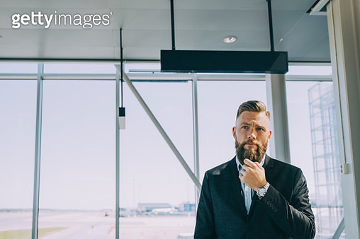 Thoughtful businessman standing against window at airport - gettyimageskorea