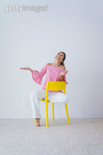 Portrait of laughing woman sitting on yellow chair - gettyimageskorea