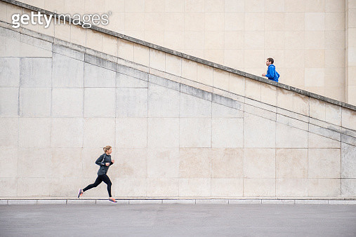 Caucasian runners jogging near staircase - gettyimageskorea