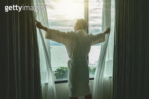 Life style and holiday concept, Back side of Asian man in bathrope suit when waking up from the bed in luxury hotel in morning - gettyimageskorea