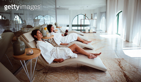 Young hispanic female friends in white robes relaxing together at wellness hotel resort spa - gettyimageskorea