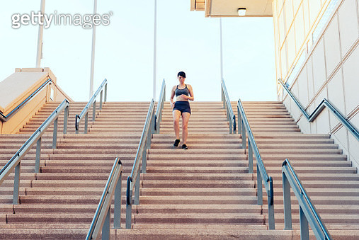 Young woman athlete running down steps - gettyimageskorea