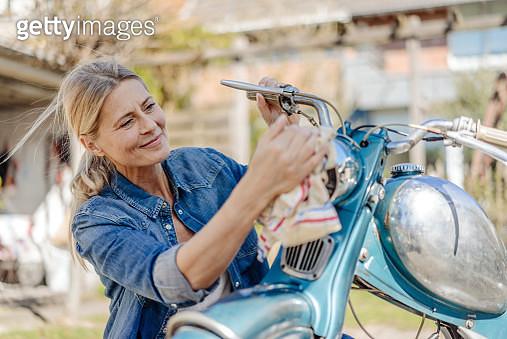 Smiling woman cleaning vintage motorcycle - gettyimageskorea