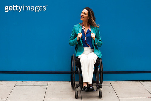 A woman in a wheelchair looking over her shoulder - gettyimageskorea
