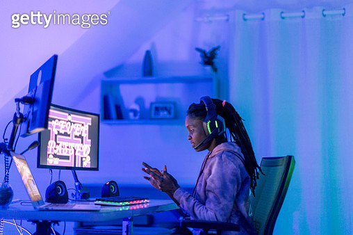 Young female gamer looking at smartphone - gettyimageskorea