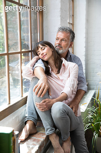 Mature couple sitting on window sill, looking out of window - gettyimageskorea