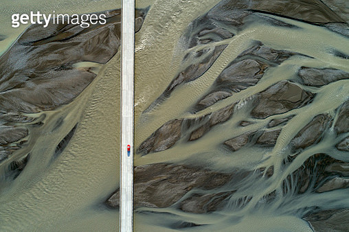 Aerial view of a small red car on the bridge and sand patterns on the river, South Coast Iceland - gettyimageskorea