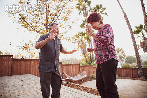 Senior couple dancing in backyard at party - gettyimageskorea