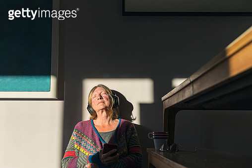 Senior woman enjoying some music with the sun on her face - gettyimageskorea